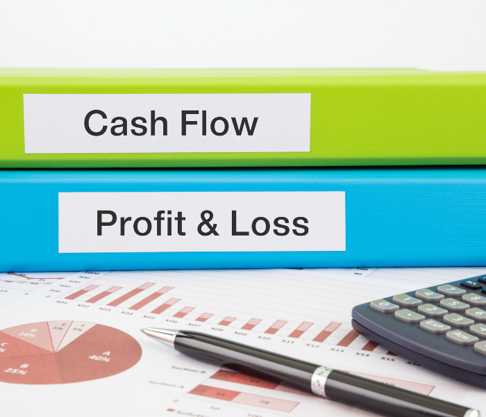 Cash Flow and Profit and Loss Binders sit on a desktop next to a customized cash flow management report