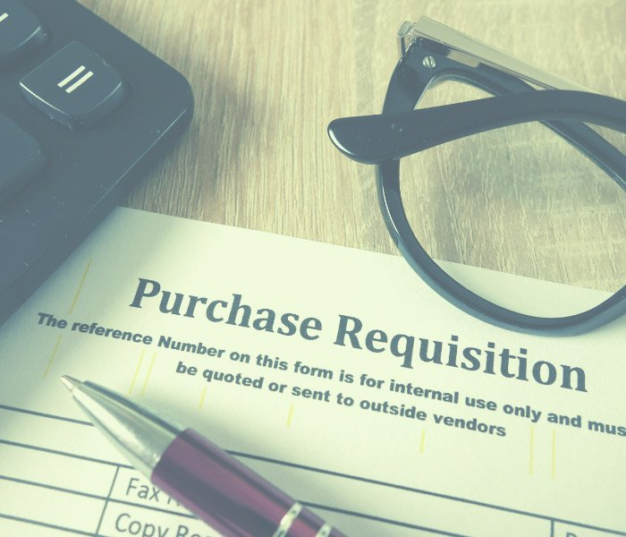 A blank purchase requisition form sits on a desk.