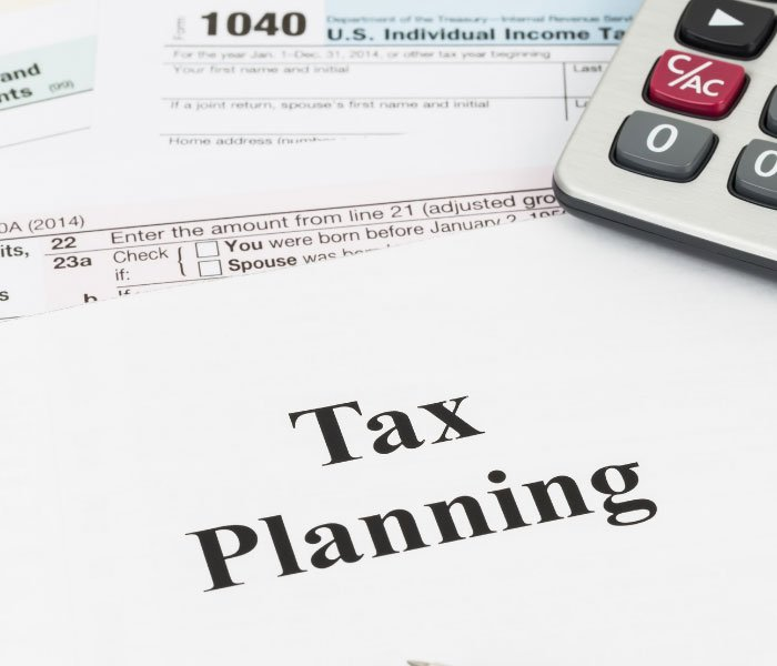"""Tax forms and the words """"tax planning"""" are seen on a document."""